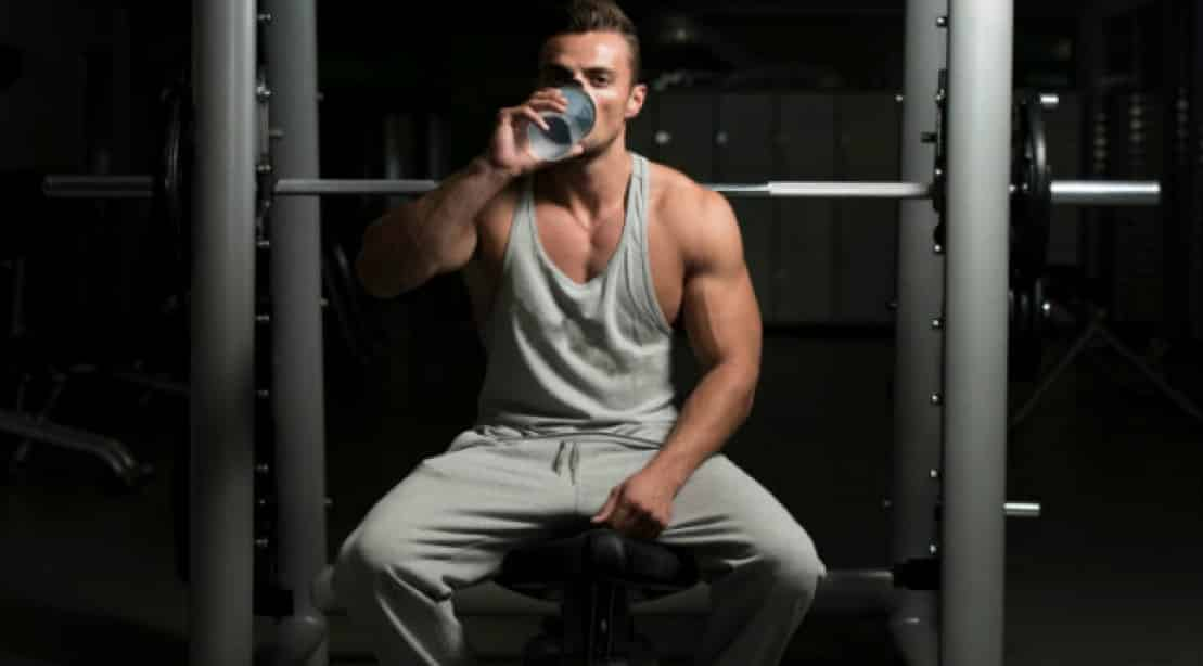 man drinks water bench