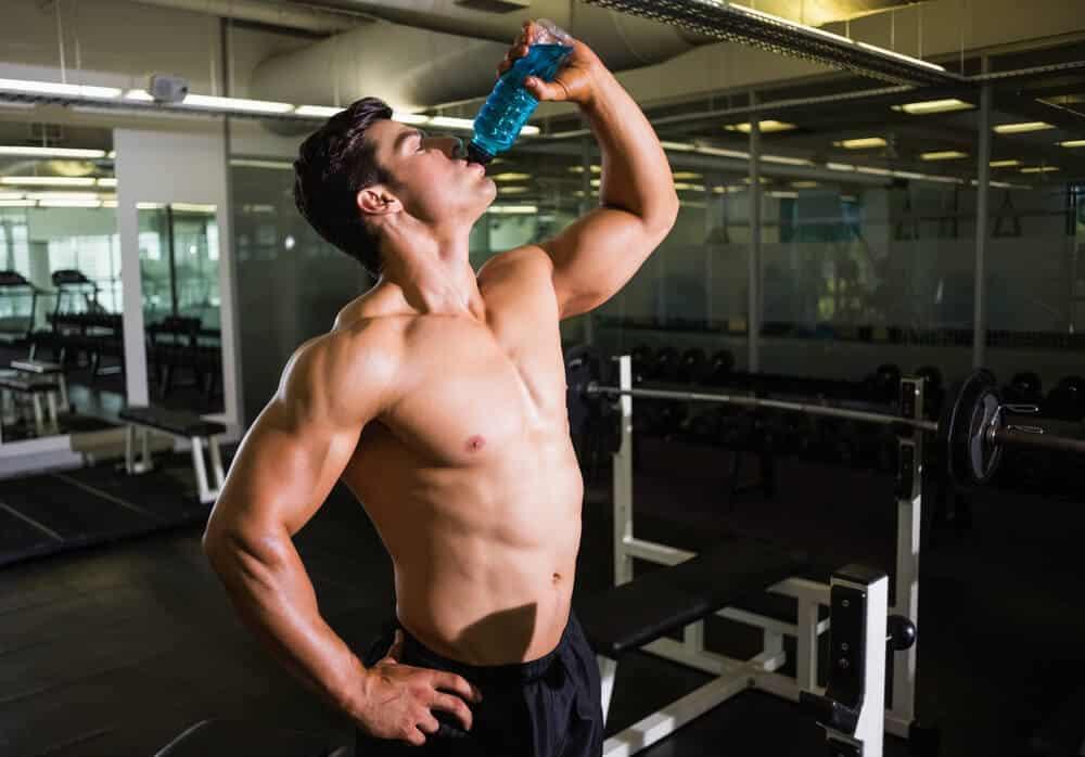 man drinks water gym